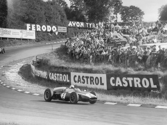 Crowds packed on grass banking to see Aussie Jack Brabham rounds one of the famous Silverstone bends during the Silver City Trophy race for Formula 1 cars in 1960. Photos: Getty Images