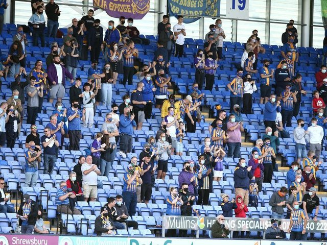 Socially-distanced Shrewsbury fans watch their team in action against the Cobblers.