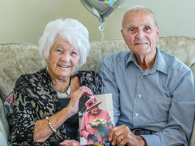 The happy couple, Joan and Roy King, pictured smiling and holding up their anniversary card from the Queen. Pictures by Kirsty Edmonds.