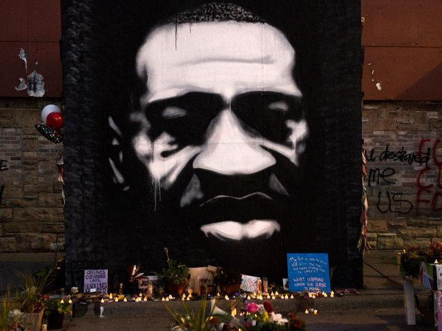 """LED candles are placed beneath a portrait of George Floyd during a birthday celebration for him at a memorial site known as """"George Floyd Square"""" on October 14, 2020 / Getty Images"""