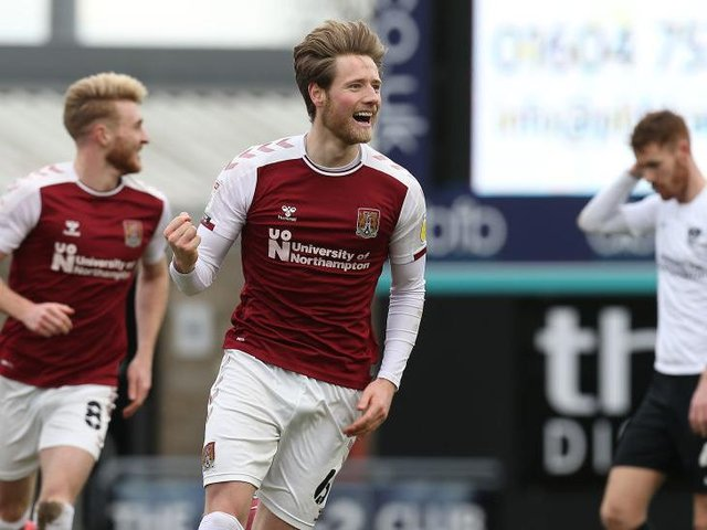 Fraser Horsfall wheels away in delight after scoring his second Cobblers goal.