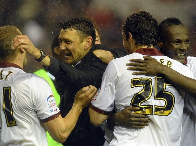 Cobblers boss Ian Sampson celebrates the win at Anfield with Andy Holt, Ben Tozer and Abdul Osman
