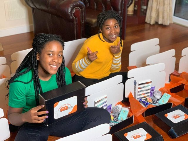 Sisters Kisten and Aiyven Mbawa with their monthly book subscription boxes.