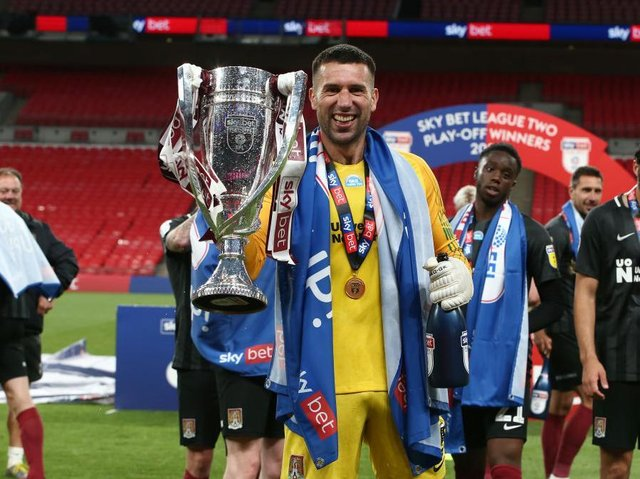 Steve Arnold celebrates the Cobblers' league two play-off final success at Wembley in June. The goalkeeper has now been released by the club