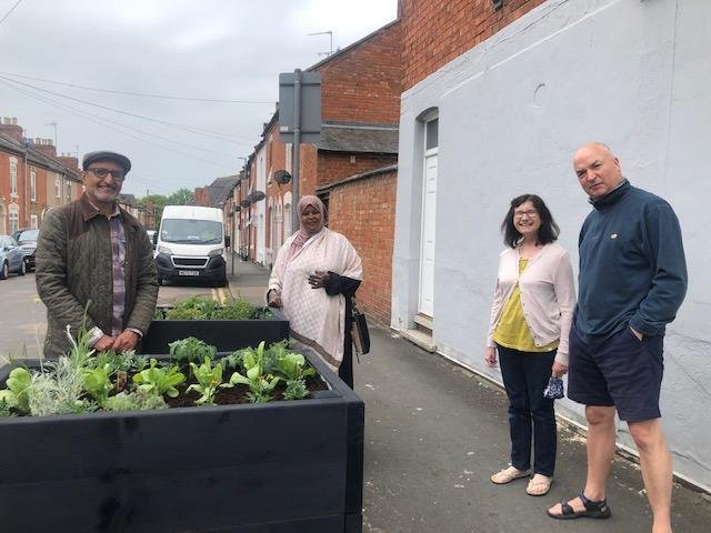 West Northamptonshire councillor Jawal Alwahabi (far left), Northampton Town councillor Fartun Ismail (centre) and two of the neighbours with the new planters on Queens Road, Northampton