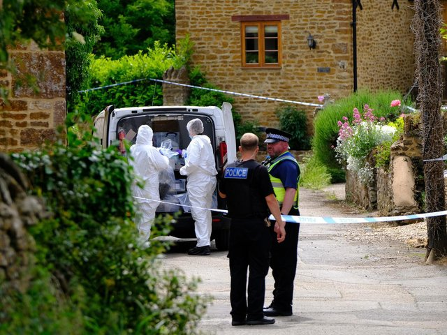 Forensic investigators gather evidence after a man's body was found in a blazing shed