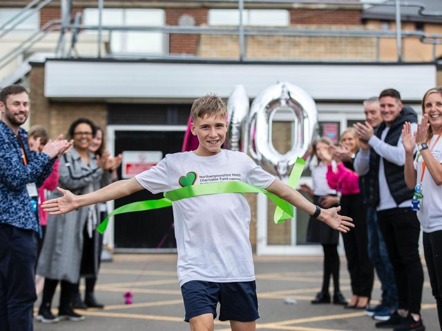 Reiss Wheatley-Crane crosses the finish line at Northampton General Hospital after running 100km in June for the children's wards' appeal for a new outdoor play area