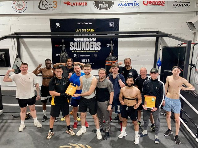 Luke Fallon (black t-shirt, black shorts) hands over the defibrillator for use at the Team Shoe-Box gym in Northampton